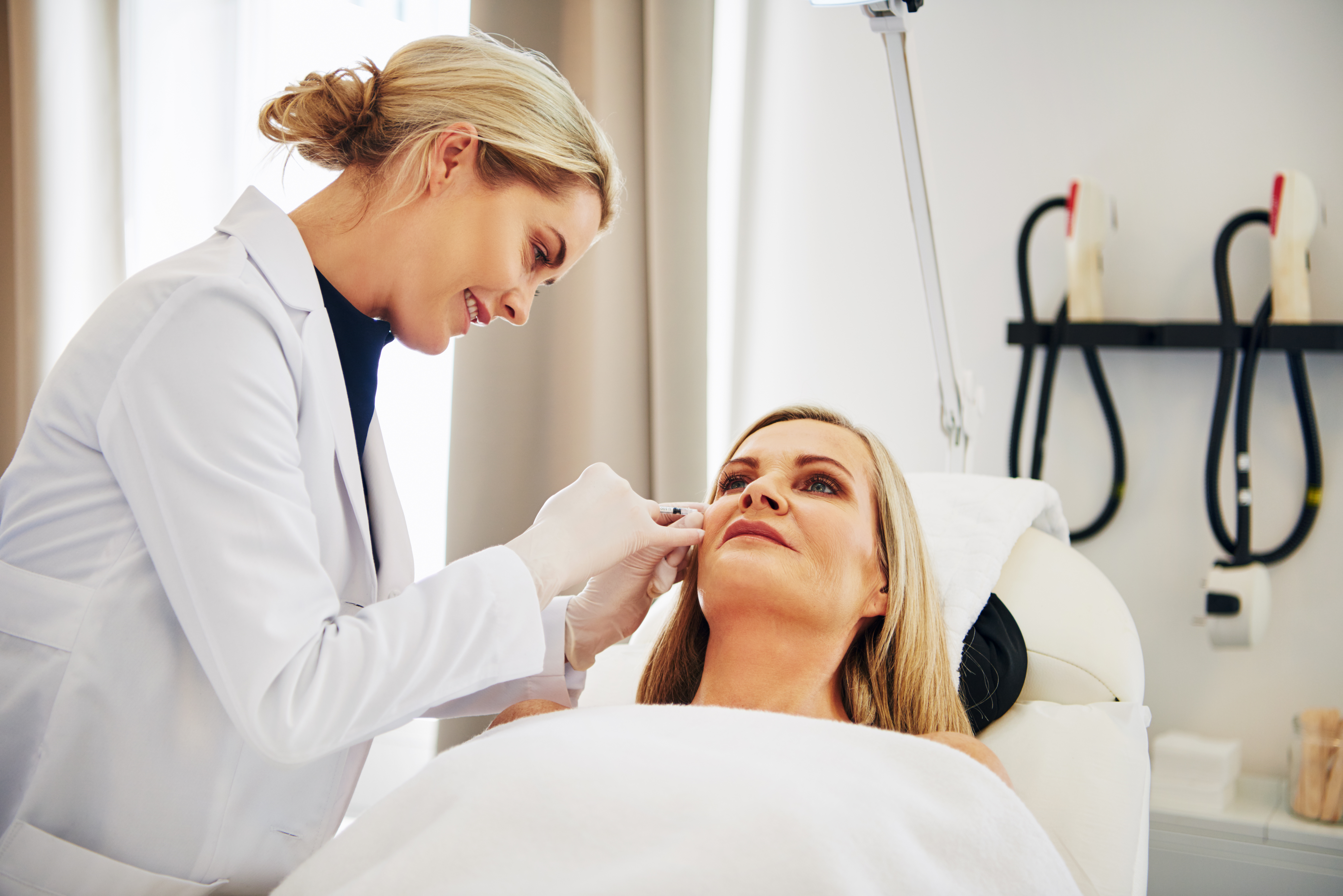 Doctor doing injections on a mature woman's face